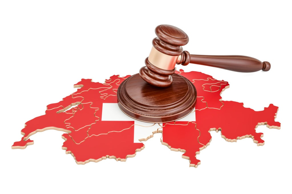 Wooden Gavel on map of Switzerland, 3D rendering isolated on white background